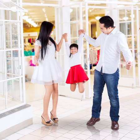 Cheerful little girl with her parents playing together in the mall photo