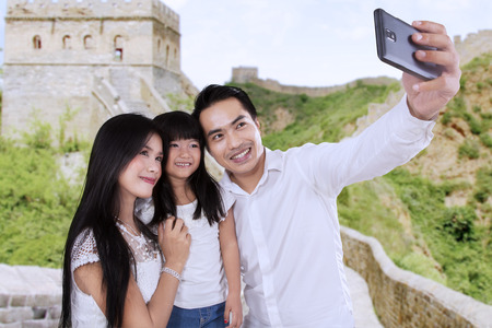 Three of member happy family taking self portrait together in Great Wall of China photo