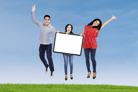 Group of happy young people jumping together and holding a blank board photo