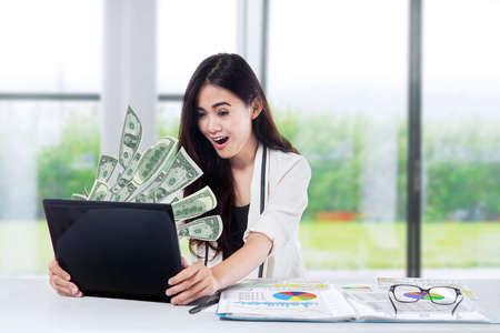 La mujer delante de la computadora portátil con mosca de dólares Foto de archivo