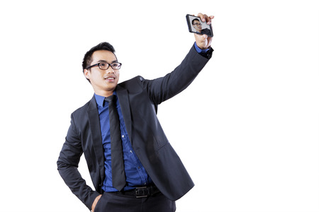Portrait of young businessman using smartphone for taking self picture photo