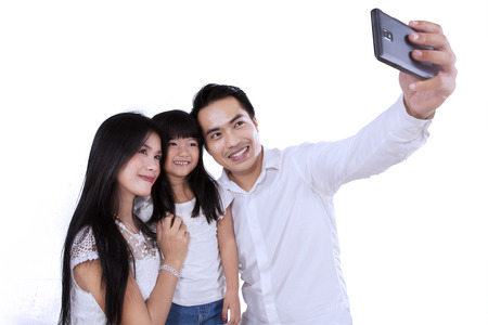 take a smile: Happy family taking picture together in studio, isolated over white background Stock Photo