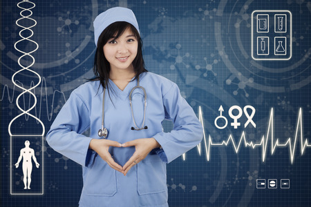Portrait of female surgeon makes heart symbol with her hands in hospital photo