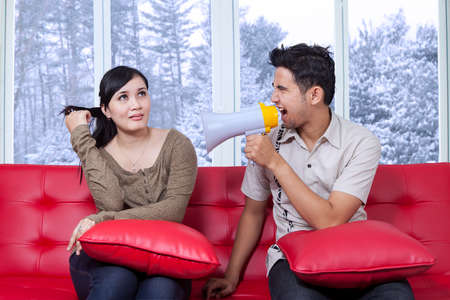 apathetic: Young man angry to his girlfriend and shouting with megaphone in winter day Stock Photo