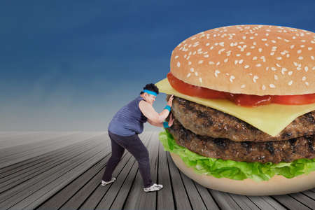 Overweight man pushing a big burger for healthy life photo