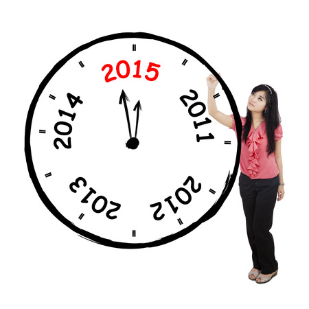 Ful length of young asian businesswoman makes annual clock, isolated on white photo