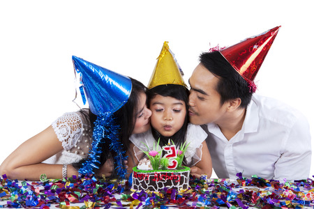 Asian girl blowing birthday candle on the cake while kissed by her parents photo
