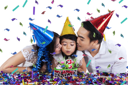 Portrait of little girl blowing candle on the birthday cake while kissed by her parents photo