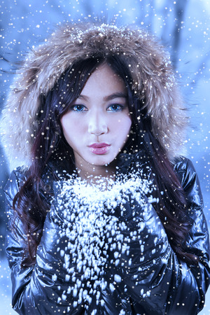 hands holding tree: Beautiful young asian girl wearing black jacket in snowy day and blowing snow to camera Stock Photo