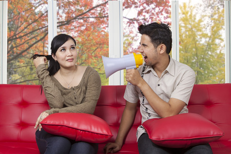 Portrait of asian man scolding his girlfriend with a megaphone at home in autumn day photo