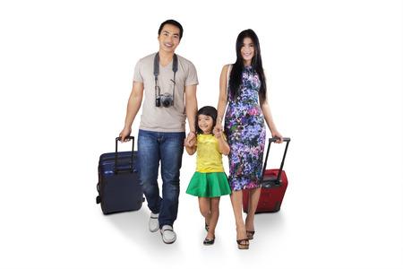 Tři člen asijské turisty chůze ve studiu při přenášení zavazadla