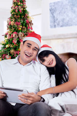 Young asian couple holding a digital tablet and smiling on camera at home in christmas day photo