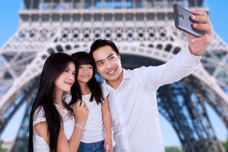 Portrait of asian family taking self portrait together in eiffel tower photo