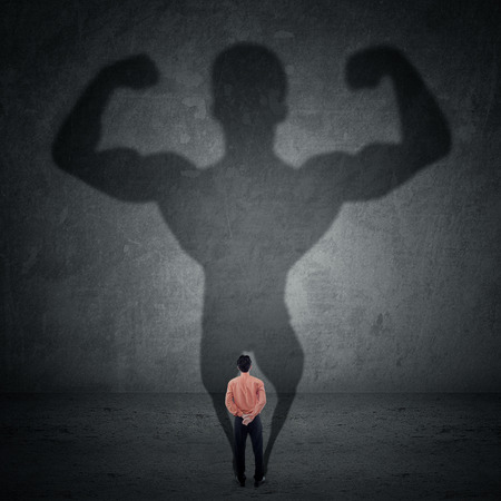 aspirations ideas: Business man casting a shadow of an athlete - business and career strength concept