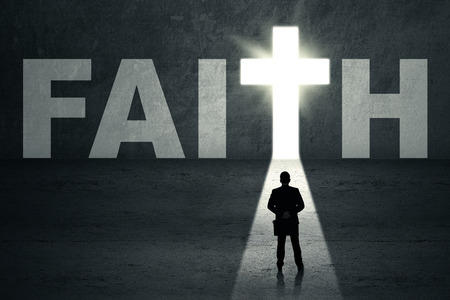 faith: Silhouette of young businessman standing in front of faith door Stock Photo