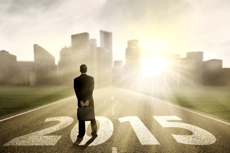 Young businessman standing on the road and looking future 2015 photo