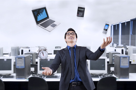 Portrait of happy businessman juggling with business items in the office Stock Photo