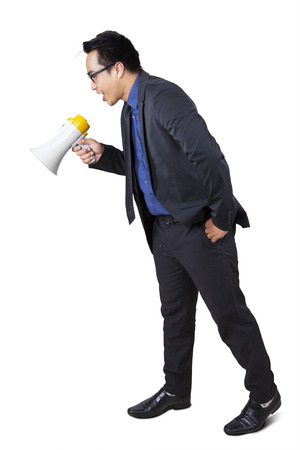 Full length of bossy businessman screaming to down with megaphone in studio photo