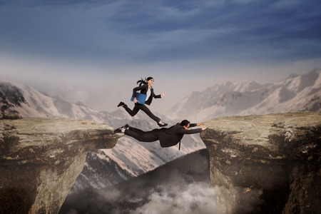 business obstacle: Two businesspeople through the gap as the business obstacle by work together Stock Photo