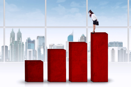 Asian businesswoman standing on the top chart and looking at the lower chart photo