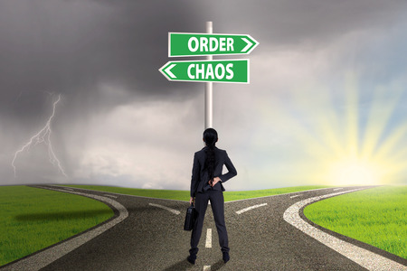 order chaos: Businesswoman standing on the road looking at signpost of order and chaos