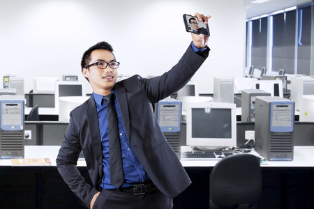 Portrait of asian entrepreneur using smartphone for taking self portrait in office Stock Photo