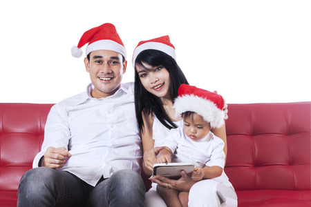 Asian family wearing christmas hat and sitting on sofa while smiling on camera photo