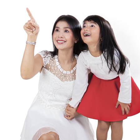 Joyful mother with her daughter pointing and looking at copyspace in studio photo