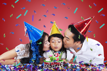 Portrait of little girl blowing candle on birthday cake while kissed by her parents photo
