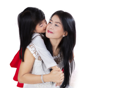 Asian child showing her love to her mother by embracing and kiss her mother photo