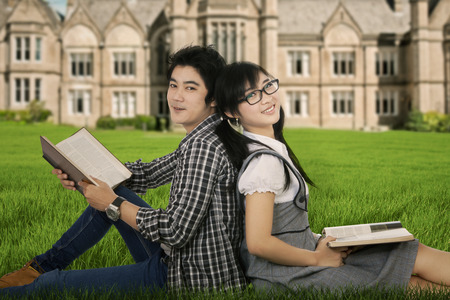 Portrait of two asian student sitting on the meadow and smiling at camera photo