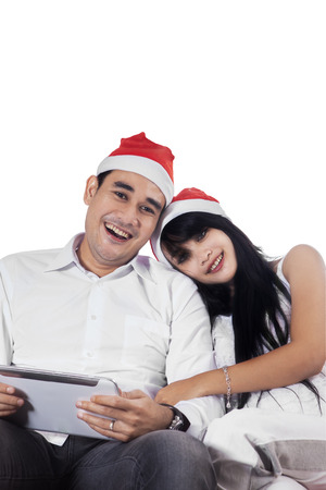Portrait of happy couple wearing christmas hat sitting in studio while holding a digital tablet photo