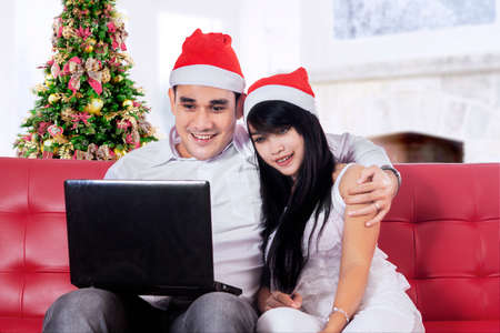 Portrait of two people sitting on sofa and use laptop computer for shopping online photo