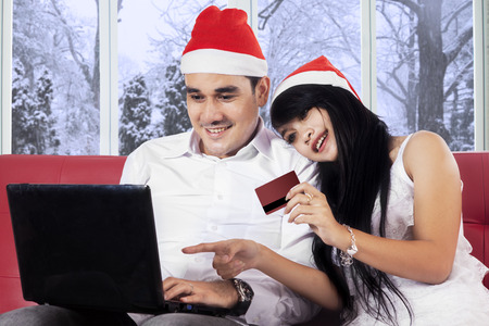 Young asian couple wearing christmas hat and using credit card with laptop for buy online photo