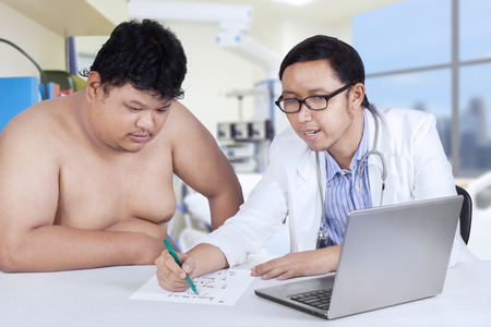 Young asian doctor writes a prescription for a fat man patient in hospital photo