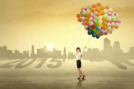 Young businesswoman holding colorful balloons outdoors, symbolizing her dreams in future 2015 photo
