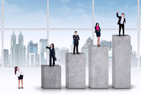 Businesspeople standing on the ranking bars, symbolizing the business growth progress photo