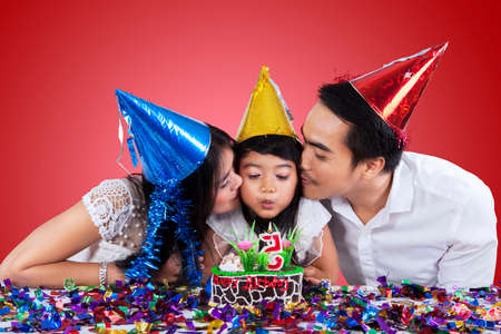 Asian family wearing party hats while celebrate little girl birthday photo