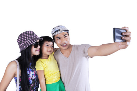 Asian family using smartphone to take self picture, isolated over white  photo