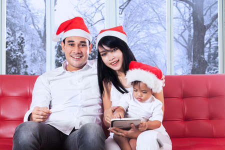 Happy family wearing santa hat and play a digital tablet on sofa with winter background on the window photo