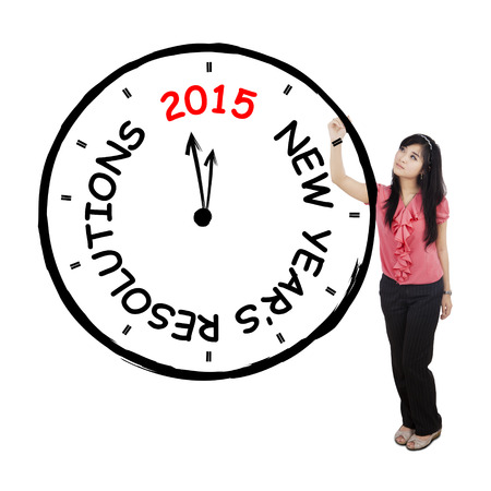 Portrait of young businesswoman makes a big clock with new years resolution text photo