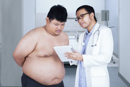 Portrait of asian doctor using a digital tablet to explain the test result to the patient photo