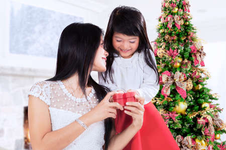 asian adults: Sweet girl giving present to her mother at home in christmas day