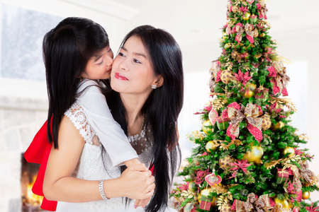Cute girl embrace and kiss her mother from back at home in christmas day photo
