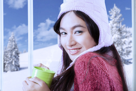 Sweet young girl wearing winter clothes while holding hot drink at home with winter photo