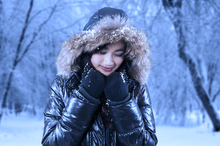 Young asian girl wearing warm jacket with fur hood, standing in winter park photo