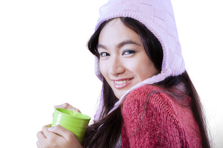 Portrait of young woman smiling at the camera while wearing sweater and holding hot drink in studio photo