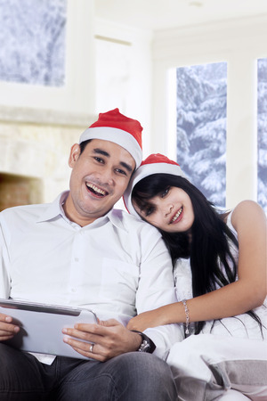 Hispanic couple smiling on camera while wearing santa hat and holding a digital tablet photo