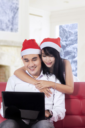Portrait of young couple using laptop for shopping online at home in christmas day photo