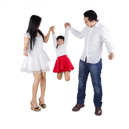 Joyful parents playing together with their daughter in studio photo